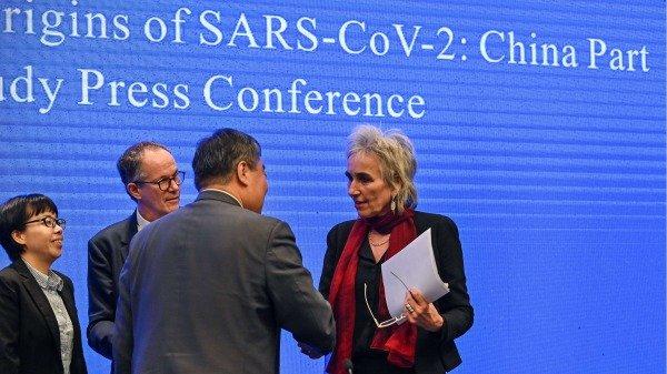 2021年2月9日,世界卫生组织专家组在武汉召开新闻会。图为世卫专家荷兰病毒学家库普曼斯 (Marion Koopmans)与中方人员握手。 (图片来源:HECTOR RETAMAL/AFP via Getty Images)