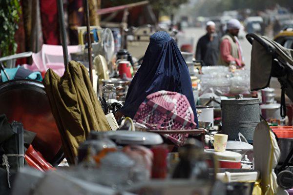 2021年9月12日,一名妇女在喀布尔西北部的一个临时市场上,查看待售的二手家用物品。许多阿富汗人以低价出售的家用品,以资助他们长途跋涉逃离这个国家,或者只是为了支付食物。 (WAKIL KOHSAR/AFP via Getty Images)